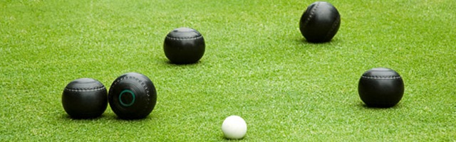 black balls on a flat green surrounding a white target ball.