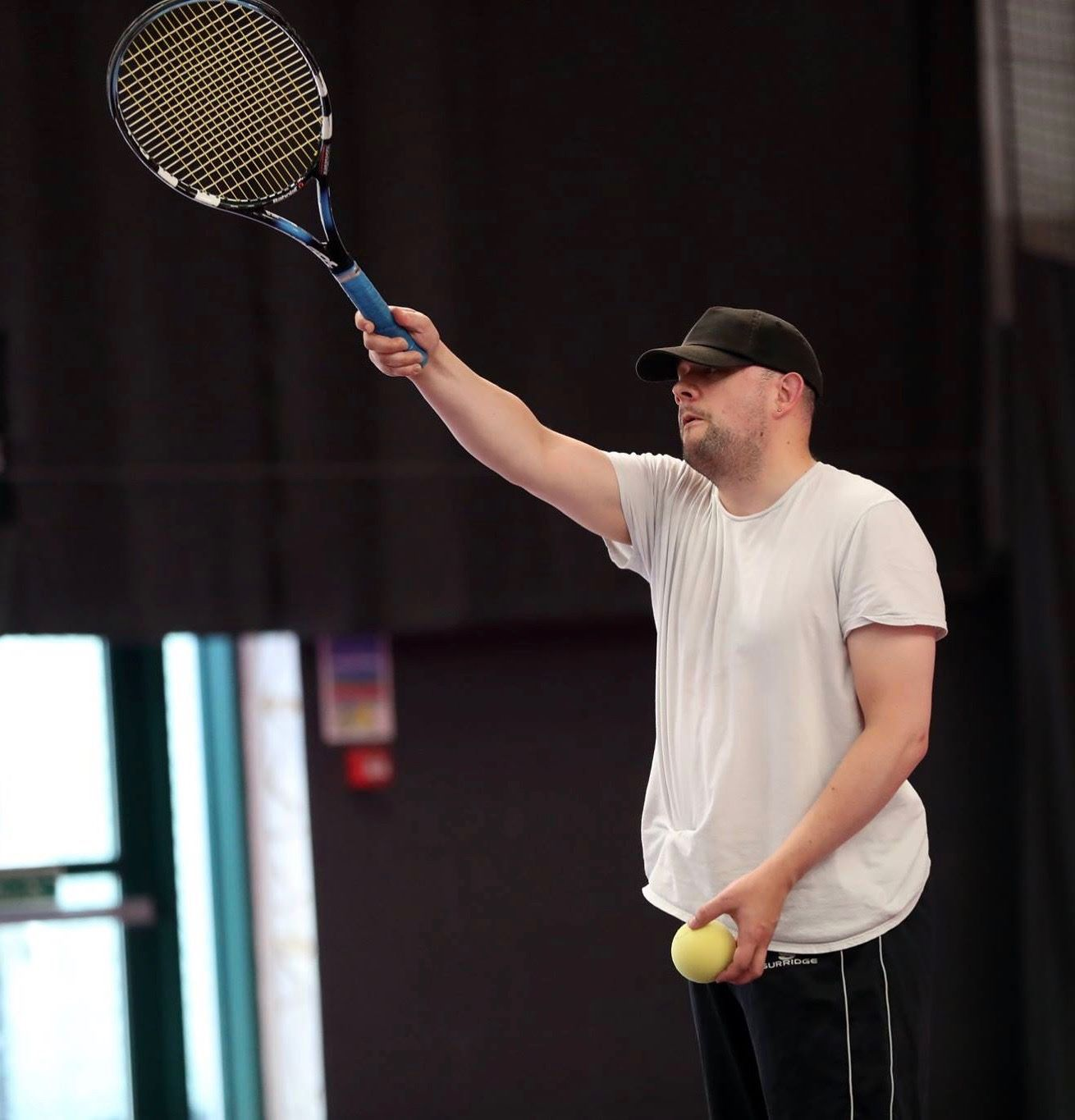A man playing tennis with a racket and an adapted ball.